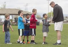 Brian Locke, a physical education teacher at Moxee Elementary School, marks the cards of students certifying each has run another lap during the school's mileage club run April 16, 2014. The mileage club, run by Locke is another way for the students to stay active. (GORDON KING/Yakima Herald-Republic).