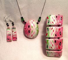 By Debby Wakley  Hollow free form polymer clay necklace, reminds me of a watermelon. Also matching tile bracelet, perfect summer colours.