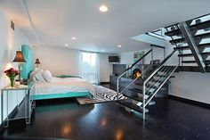 Modern bedroom with nice contrast between the dark floor and the white. Also a very cool staircase