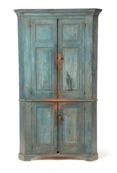 American Corner Cupboard, 1st half-19th century, poplar.  One piece with raised panel doors and old blue over earlier red paint.  78 H. x 45 W. x 21 D.  Requires a 31 inch corner.