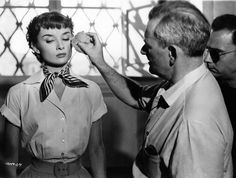 Director William Wyler touches up Audrey Hepburn's makeup on the set of Roman Holiday (1953).