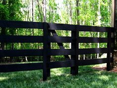 4 board fence and gate.  Wood stained black.  Has mesh.  Hmmm.
