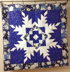 January wall hanging quilt done in blues and whites.  Large, easy, snowflake pattern made from squares and triangles.  Made by Virginia Smith with Show Me Sewing.