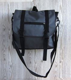 This stylish backpack easily transforms to a messenger bag! Can be used as laptop bag or Ipad bag. Bag has a padded back and a padded section for your tablet or small laptop. It also has big zippered section at the back to keep your most precious things secure. It is made of water resistant charcoal and black fabric. Its large and roomy, and it also has many pockets, so you definately will find the right place for all your belongings.  All the using parts of the bag are double or triple…
