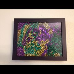 Mardi Gras decorations - beads in a shadow box. this is pretty neat.