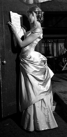 Model reading music in evening gown by Charles James, 1950. James looked upon his dresses as works of art, as did many of his customers. Year after year, he reworked original designs, ignoring the...