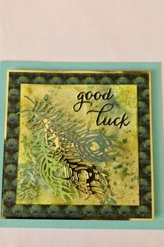Graphic 45 paper and spellbinders feather die combined with a messy handmade background to make this wonderful good luck card