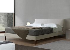 'Joel' Bed with wooden structure. Padding foamed with polyurethane in different density. Cover in fabric completely removable, leather or leather-look. Tailored stitching. Feet in tobacco oak, dark oak, walnut.
