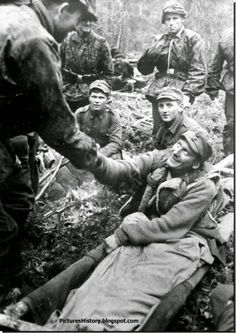 A soldier from the 6th SS Mountain Division 'Nord' shakes the hand of a wounded comrade.