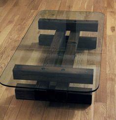 Mesa de centro con patas de madera y sobre de vidrio.