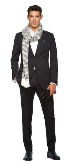 Black suit, white dress shirt, and black dress shoes with grey knit scarf and black leather gloves.
