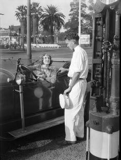 Female motorist stops for gasoline in Los Angeles CA ca. 1920s