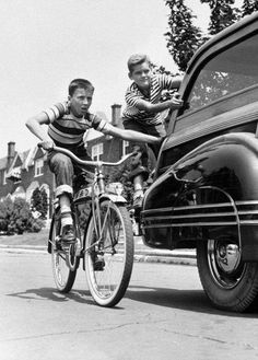 Boys on bicycle hitching ride on Pontiac Woody, ca. 1940s