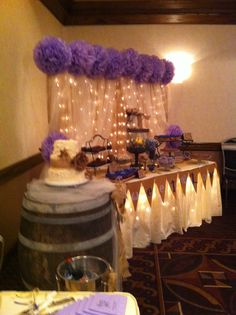 Candy bar with Sweet Love banner and icicle lights under table and net lights on back drop. Back drop is covered in burlap with organza curtains and tissue flowers!