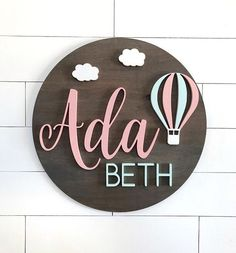 This custom name sign features a handmade, round name sign with hot air balloon and clouds. These signs are the perfect addition for your kids room or nursery room decor. They also make great gifts for a baby shower or birthday! Each piece in our collec Nursery Signs, Nursery Room Decor, Nursery Wall Art, Clouds Nursery, Baby Name Signs, Baby Names, Name Boards, Wood Names, Baby Wall Art