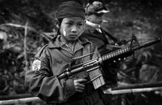 A Karen child soldier in the Thai-Burma Border. It is easy to pretend such things do not exist, but we must take action when we see a child like this with his ancient eyes, playing at a war he does not understand. Photo by mikel flamm, 2000.