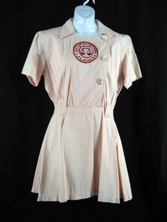 Madonna's screen worn baseball uniform from A League Of Their Own All American Girls Professional Baseball League Rockford Peach uniform, number 5, worn by Madonna as Mae 'All-The-Way-Mae' Mordabito.  Uniform consists of a peach colored knee length dress with a large Rockford Peaches patch in the center, large '5' sewn on the back and a smaller AAGPBL patch on the left shoulder, three button front and matching belt.