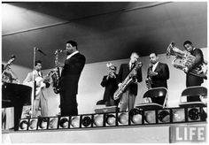 Sonny Rollins (5R) Dizzy Gillespie (4R) and Gerry Mulligan (3R) Ben Webster (2R) at the Monterey Jazz Festival by Nat Farbman 1958