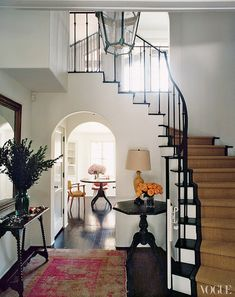 I Love the FEEL of this foyer. The drama of the stair case, light from 2nd floor window, the arched doorway, dark floor, rug, all the furniture. I want to go on in to the kitchen & see what is in there too.....