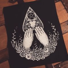 I just screenprinted more of the Spirit Medium back patches! You can find them in the web shop (Link in Profile) The ghostly pale hands of a spirit medium rest upon an ornate planchette. The medium is an experienced psychic and particularly adept at communicating with spirits of those whos souls reside on the other side of the veil. Her hands stretch forth from a bouquet of funerary flowers and gently rest upon the planchette a tool of her magical trade. Within the oracle eye of the…