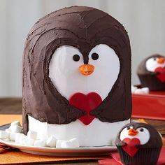 Penguin Valentine's Day Cake - Sweet and simple. This Penguin Cake will win their heart. Easy buttercream icing and a fondant cutout heart make it super easy to decorate an adorable Valentine's Day-themed cake that's sure to warm their hearts.