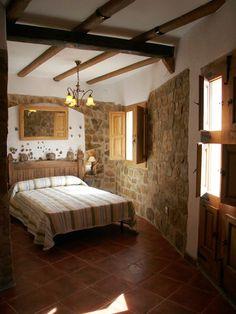 Habitación con techos con vigas de madera y paredes de piedra. Ventanales de madera.