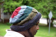 Manly - Yes, but we like it too!  Make this colourful cabled cap by Rohn Strong  in a worsted weight yarn.