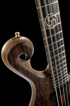 Scroll, fretboard inlays and ebony-covered neck pickup of the custom bass guitar