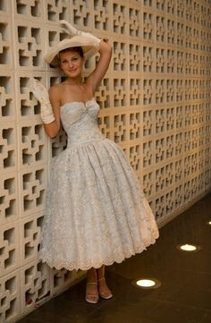 Bella Tea is a strapless, Tea-length wedding gown accented with a vintage brooch. The white beaded lace dress is detailed with silver cording all over. The tint of blue you see is the blue lining underneath the lace.