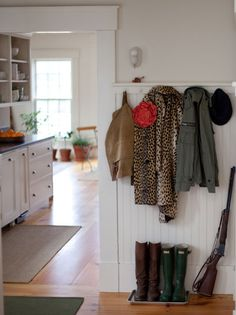 a great entryway! (minus the shotgun...) wainscoting gives such a country feel.and i love the idea of using a tray to keep your boots on!