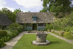 A view across the Well Court with the Venetian well-head, looking towards Virgin Mary in a gable in the garden house at  Snowshill Manor, Gloucestershire, UK