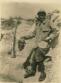 A morbid souvenir : a French soldier holds a Prussian skull still covered by his leather helmet.