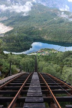 Mågelibanen in Hordaland, Norway Train rails sliding down a mountain with breath taking views of lush green mountains and reflective lake and small village below.