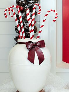 Take inspiration from classic Christmas candy for your outdoor holiday decorating. Fill a white planter with decorative candy canes for a uniqueholiday front porch display. Best Outdoor Christmas Decorations, Christmas Greenery, Decorating With Christmas Lights, Christmas Porch, Farmhouse Christmas Decor, Porch Decorating, Light Decorations, Holiday Decorating, Christmas Candy