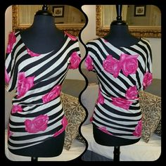 """Asymmetrical Fitted Striped Top This beautiful top has a drastic asymmetrical hemline that hangs from 23"""" long to 32"""" long. Black and white striped with bold pink roses. Made from 100%Rayon  I got this top when I had my shop. It is NWT from the distributor. On the left sleeve there is a small hole about 1 cm long that looks like it wasn't sewn shut during manufacturing. I can fix this with a few stitches, or send to you and you can fix it, will be super simple and not noticeable. *price…"""