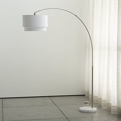 Shop Meryl Arc Floor Lamp.  The arc floor lamp goes over and above modern expectations, suspending a geometric two-tier shade in crisp white cotton blend from a satin nickel-finished arch.  Round grey marble base adds a classic touch.