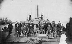 USS Atlanta ship's officers on the foredeck, while she was serving on the James River, VA., in 1864-65. Atlanta's armored casemate, forward rifled gun, and pilothouse are visible behind the officers.