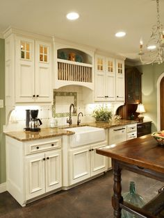 To give this beautiful kitchen a custom look, the porcelain tile backsplash was hand-painted. A plate rack over the farmhouse sink is useful and charming, while Craftsman cabinets incorporate a multi-pane window at the top.