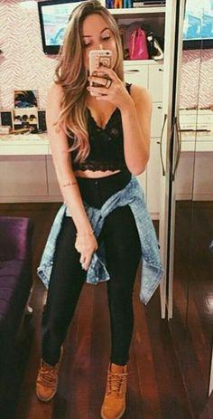 Top preto com calça de cintura alta preta e jaqueta jeans amarrada na cintura