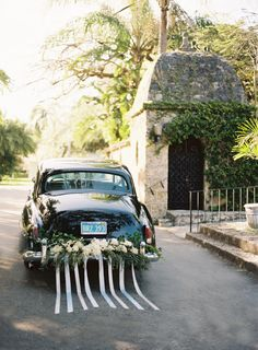 Vintage getaway car decorated with flowers and ribbon, #justmarried