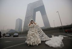 Performance artist in front of Central Chinese TV building in Beijing. She wears a wedding dress with a gas mask to protest the pollution. Chinese Bride, Running Photos, Good Environment, Spring Summer 2015, Beijing, Brighton, Catwalk, Wedding Gowns, Fashion Design