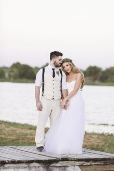 bride and groom holds hands on lakeside dock @myweddingdotcom
