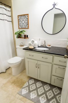 DIY bathroom remodel reveal. Updated on a tight budget, all DIY updates, paint, tile backslash, shelves, art, and shower curtain.