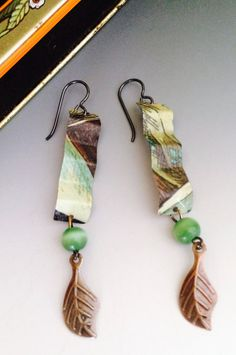 Up-cycled green and brown earrings accented by a brass metal leaf