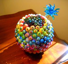 Round Sculptural Rolled Paper Rainbow Vase - upcycled from paper collected from magazines, catalogs, giftwrap, etc. Flower - upcycled from plastic water bottles. - Blue Reco
