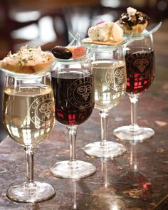 Appetizer plates sit atop wine glasses with a good appetizer and wine pairing.
