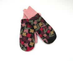 These wool mittens feature beautiful felted flowers in mustard yellow, rose pink, fuchsia pink, and plum with soft green leaves on charcoal gray boiled wool. The floral pattern in accented with a fine decorative silver thread throughout. The palms and cuffs are pale rose pink lambswool. Lined with black polar fleece. Accented with 1 inch matching covered buttons. Standard womens size. Fingertip to top of cuff approximately 8 1/4 inches, cuff 3 inches Warm wool mittens made from high-qu...