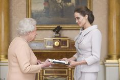 Angelina Jolie was given her DCMG during a private midday audience with Queen Elizabeth in the 1844 room at Buckingham Palace today, 10 October 2014.