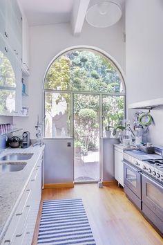Una #cocina conectada con el jardín gracias a esta puerta que garantiza luminosidad en la estancia.