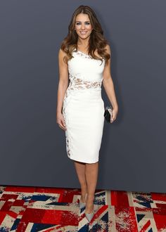 """Elizabeth Hurley will return to television as a queen — a title she deserves in real life as well. At 49, her skin is flawless, body as fit as her 20-something costars, and can still wear a tight bodycon dress with the best of them. At a special screening of her new show The Royals on Monday night in New York City, she showed up in a one-shoulder LWD with lace cut outs paired with gray heels. """"For me this is like sex, drugs and rock 'n roll at Windsor Castle."""" And if Hurley's latest red…"""